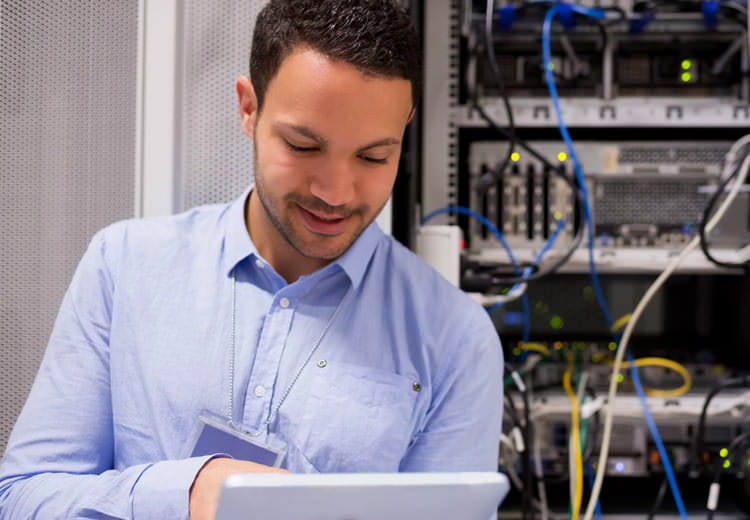 An IT administrator smiles while looking at a tablet as he stands in front of a server rack