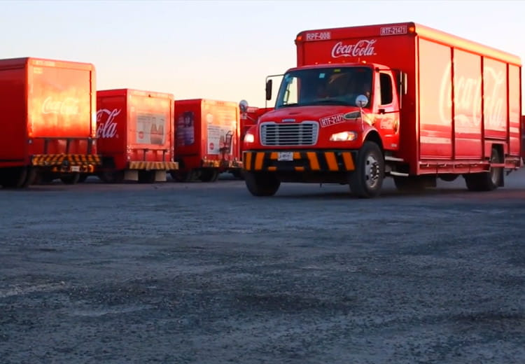 The sun rises over a lot full of Coca Cola delivery trucks