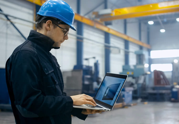 An engineer in a manufacturing plant reviews data on a laptop