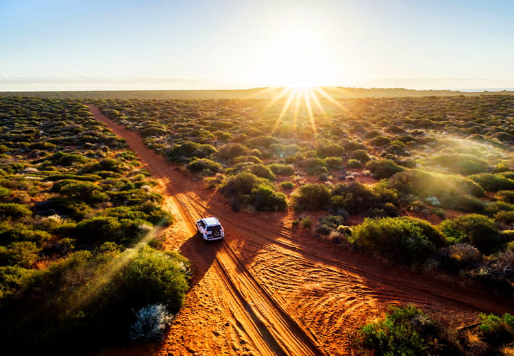 An SUV drives down a dirt road surrounded by green brush through the Australian outback as the sun rises on the horizon
