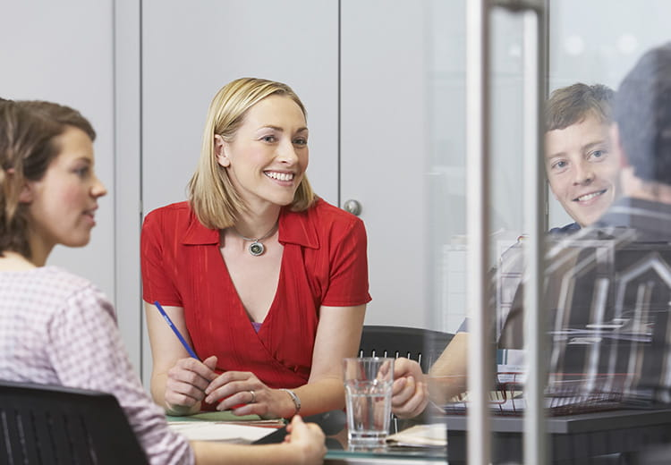 Meeting room with woman in red shirt smiling