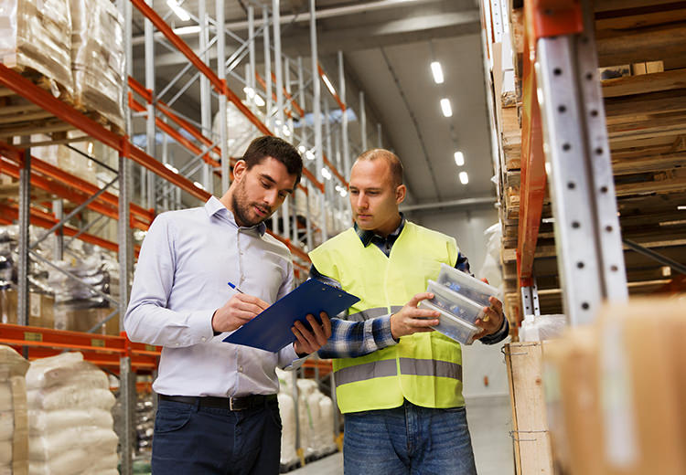Two employees in a warehouse review a shipping schedule