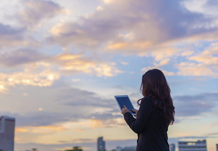 Woman on tablet with clouds in the sky