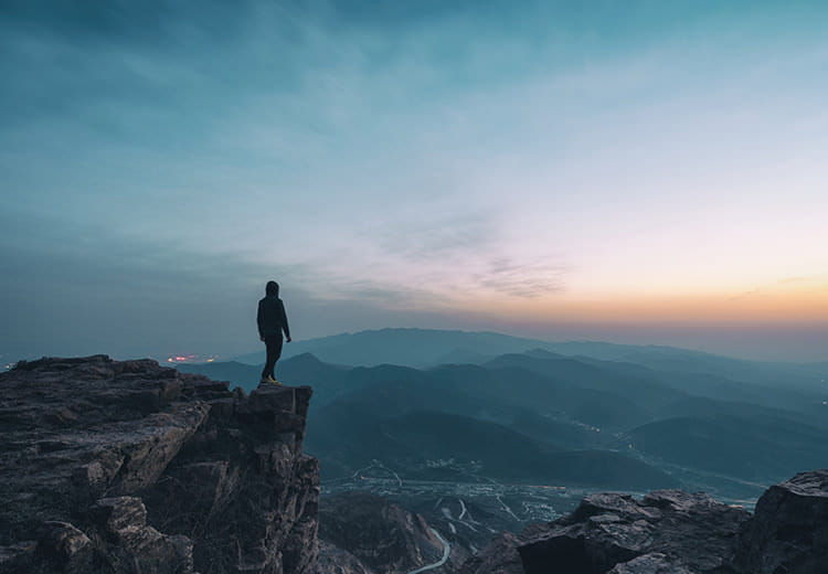 Person looking out at sunrise from the mountains