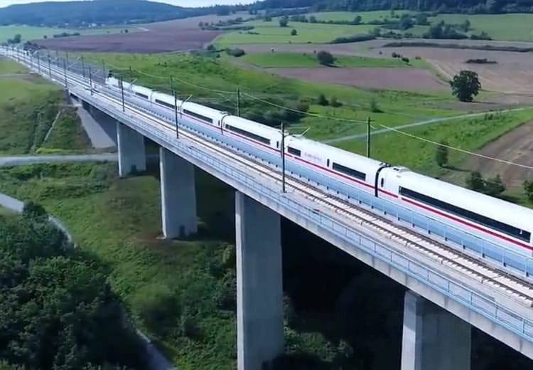 Deutsch Bahn train travels over bridge in countryside