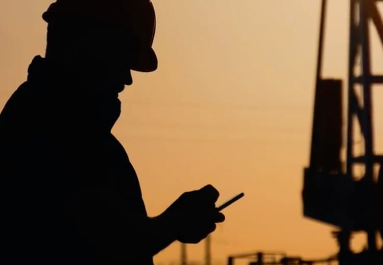 Worker wearing hard hat looks at smartphone at sunset with oil rig in background