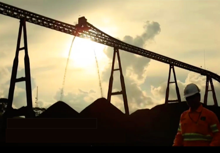 Coal mining equipment in silhouette with worker walking in the foreground