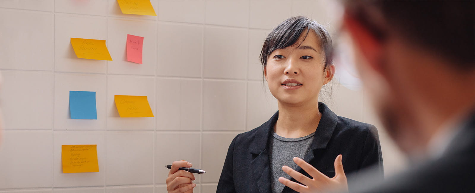 Wide shot of woman lecturing next to post-it notes with a pen in her hand