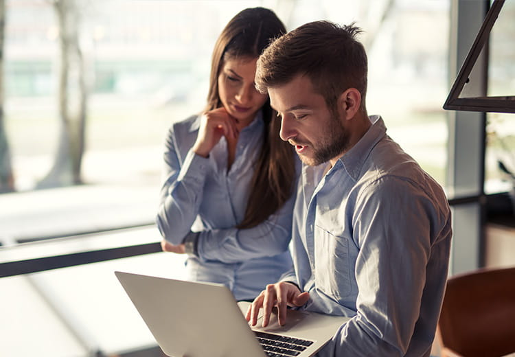 Man and woman working on laptop in office