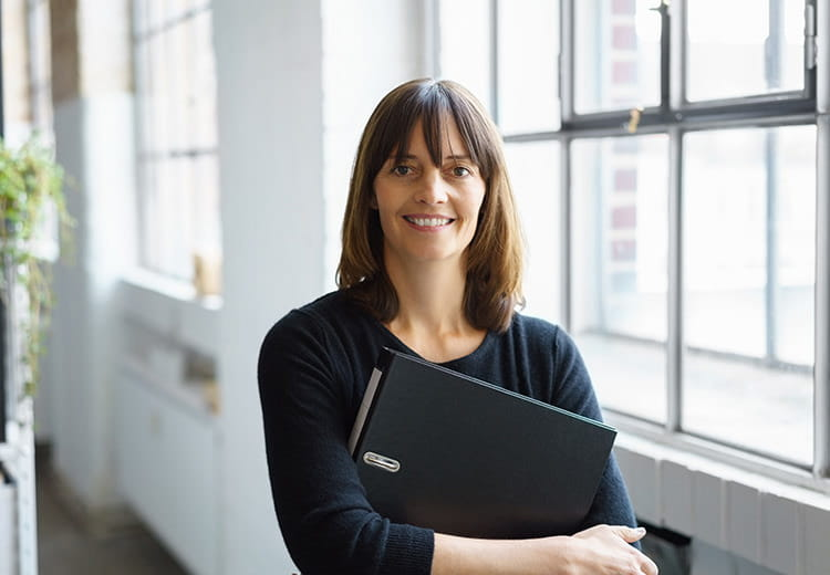 Woman in black shirt smiling while holding laptop