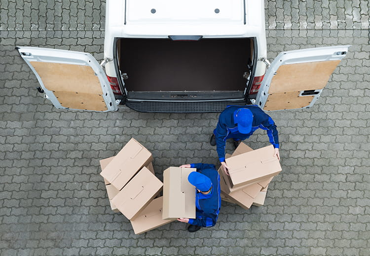 Overhead shot of man dressed in blue loading a van