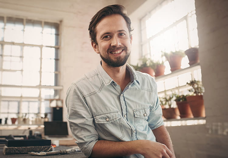 Guy in a light blue shirt smiling in a kitchen with plants