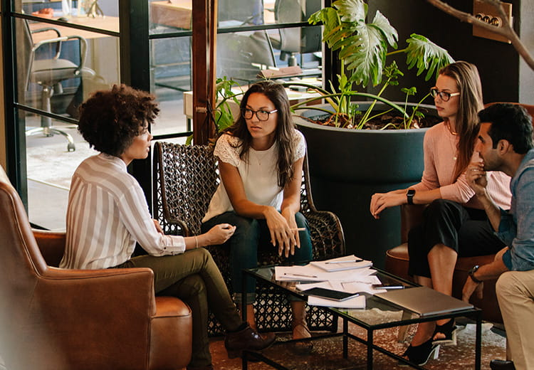 Three women sitting around coffee table talking
