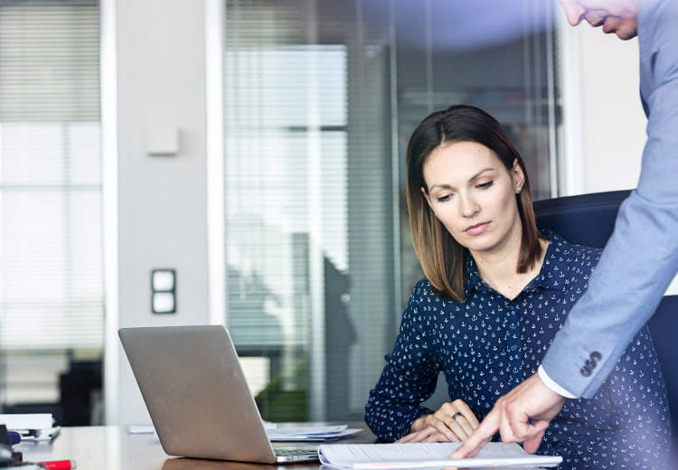 Woman in blue shirt looking at paperwork while at laptop
