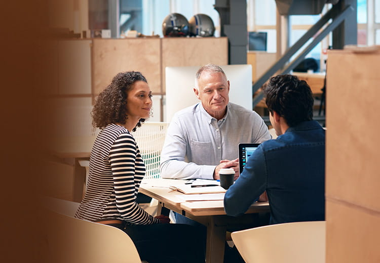 Three co-workers meeting at a table with laptop