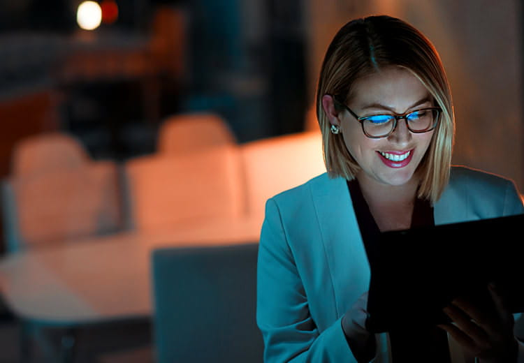 smiling woman working with laptop in image used to promote SAP Ariba guided buying capability