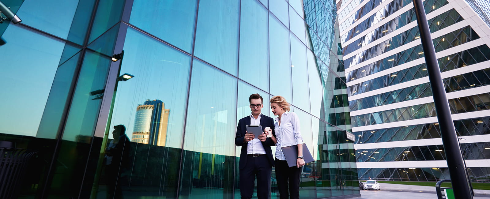 Wide shot of man and woman outside building looking at tablet