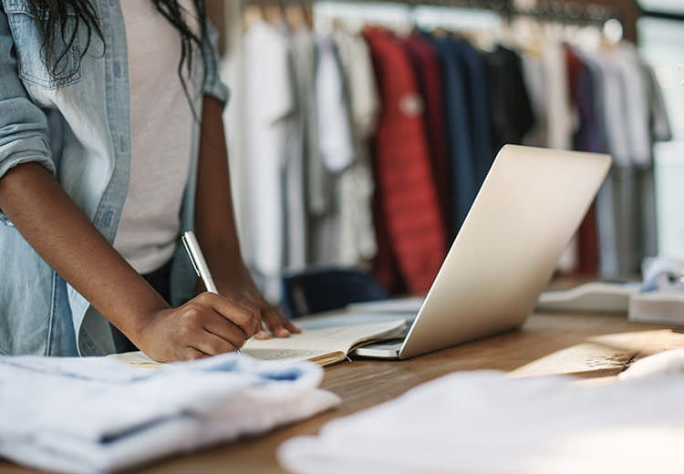 Laptop on table with clothing in the background