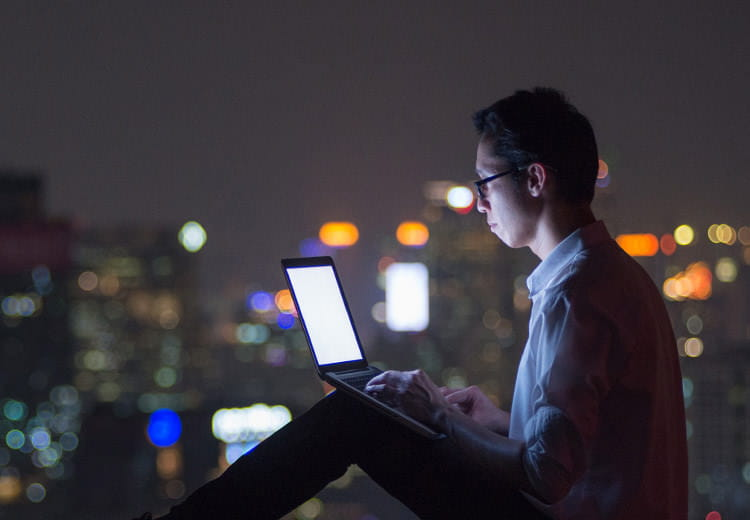 Man on his laptop at night with city skyline in background
