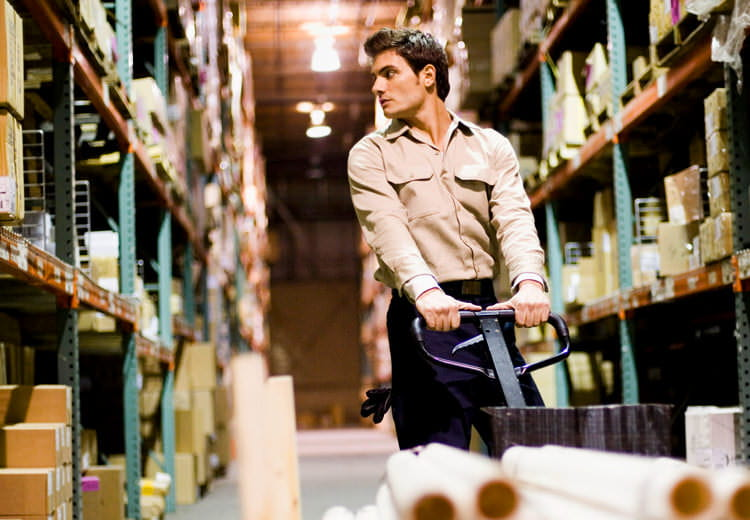 Image of man in warehouse suggesting concept of managing all spend in one place using SAP Ariba procurement software and solutions