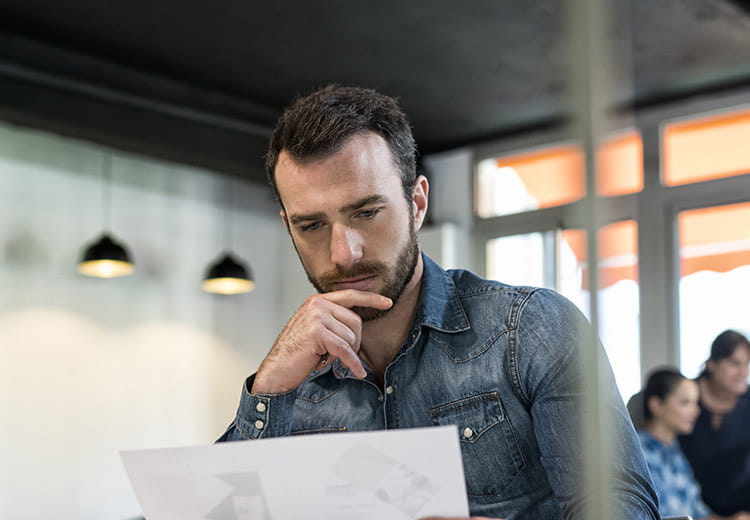Man in collared shirt examining paperwork