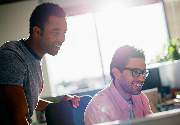 Two young men in an office smile as they look at a computer monitor