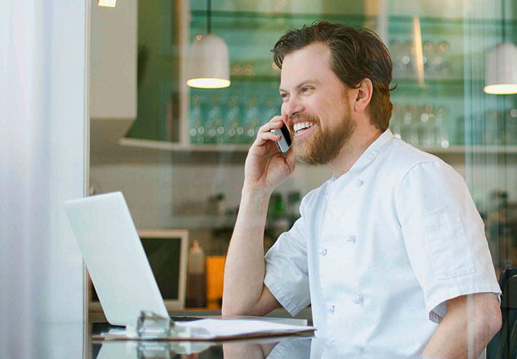 Happy man on cell phone looking at laptop in cafe