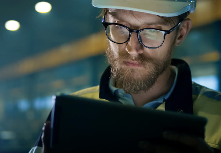 A closeup photo of a worker wearing a hard hat reviewing integration solutions on a tablet