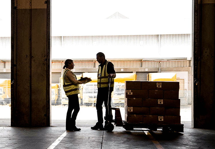 Two people on a loading dock next to a crate