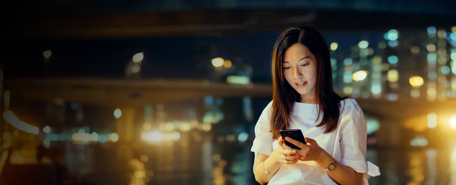 A woman uses her mobile phone standing outside at night with the city lights blurred behind her.