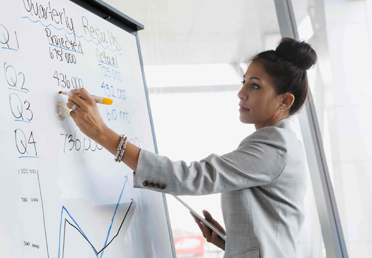 An executive writes down financial data on a large white board.