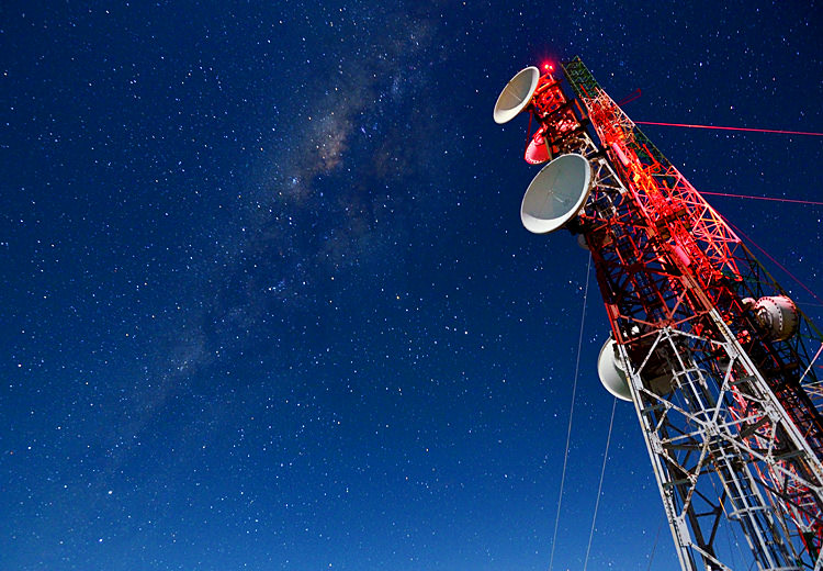 A large red radio cell tower rises against the blue twilight sky as the Milky Way appears.