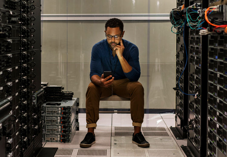 IT professional in server room looking at tablet
