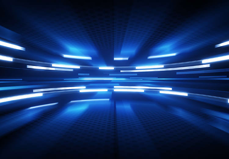 Abstract high-tech image of blue lights blurred against a black background showing movement