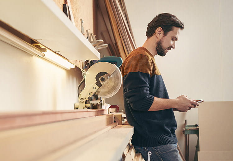 Man in two-tone shirt looking at phone in workshop environment