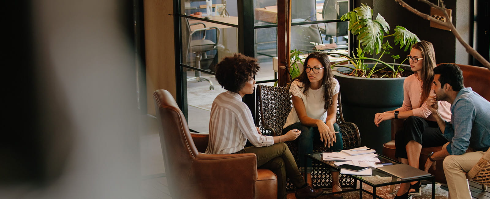 Wide shot of three women sitting around a coffee table talking