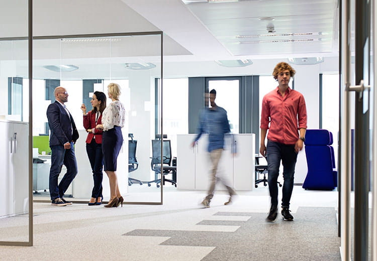 Five office workers standing in a clean office space