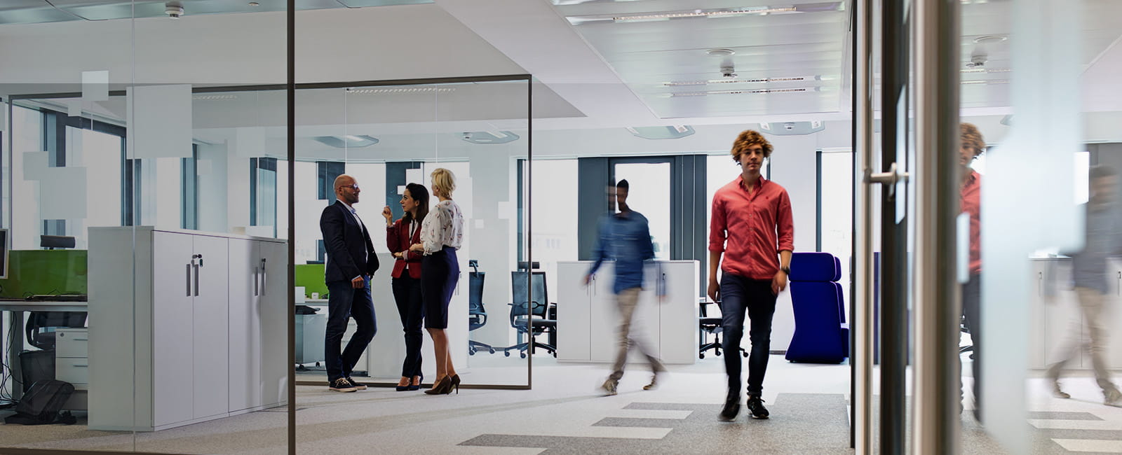 Wide shot of five office workers standing in a clean office space