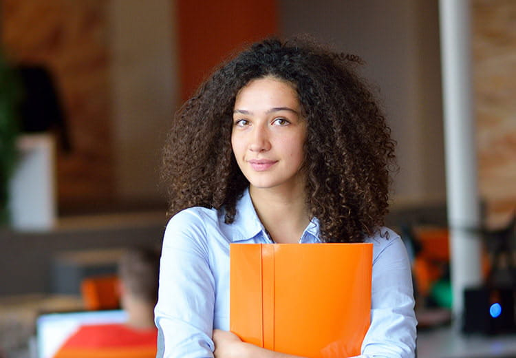 Girl in blue shirt with orange notebook