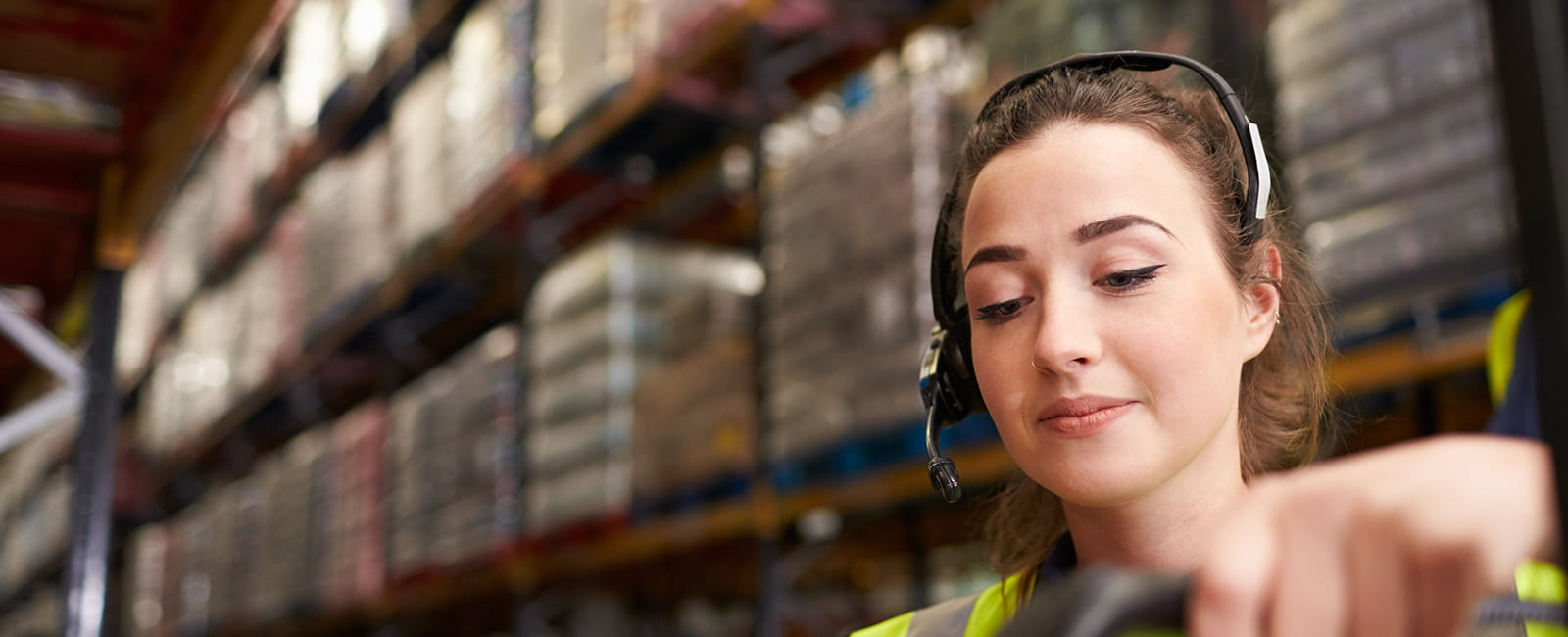 Wide shot of woman with headset working in warehouse