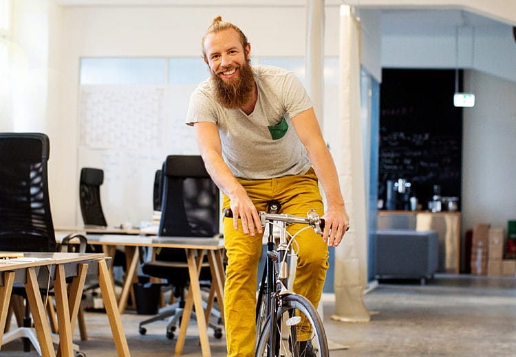 Man with beard riding bicycle through office
