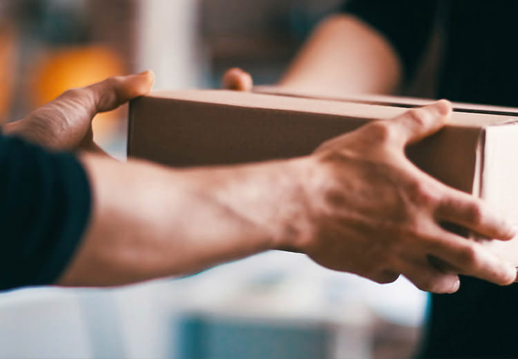 A close up of hands accepting a box that has been presented illustrating the simplicity of SAP Ariba supplier management
