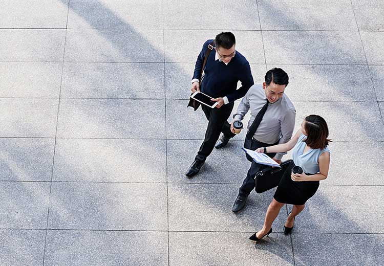 Overhead view of three co-workers walking outside as they discuss SAP Ariba Guided Buying