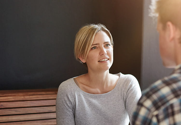 Woman in gray shirt talking to a man