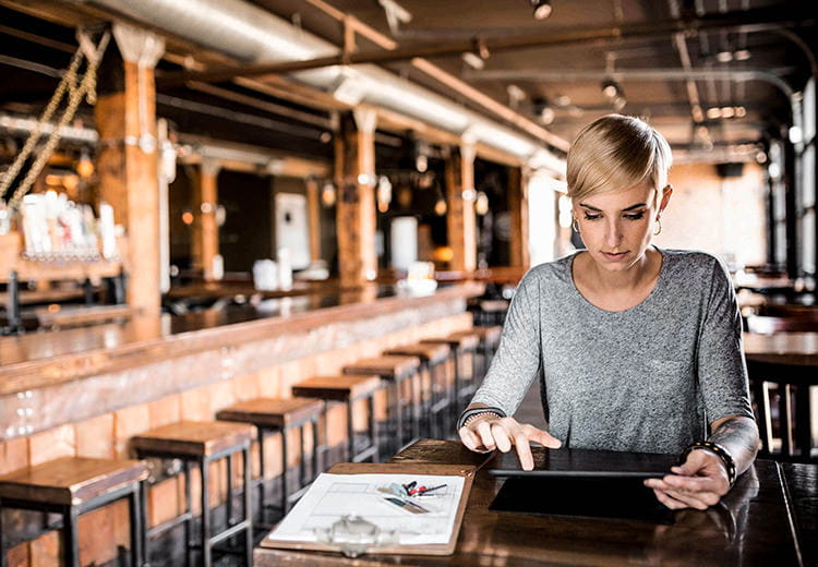 Woman on her tablet at a restaurant