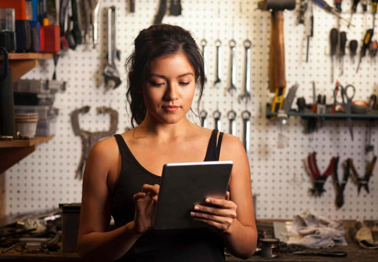 A mechanic uses a tablet to order tools online