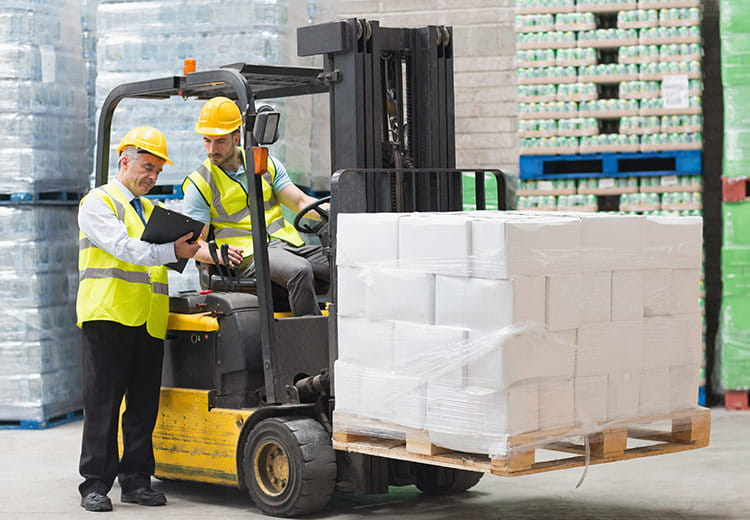 Two men, one on a forklift carrying a pallet stacked with material, review items on a clipboard