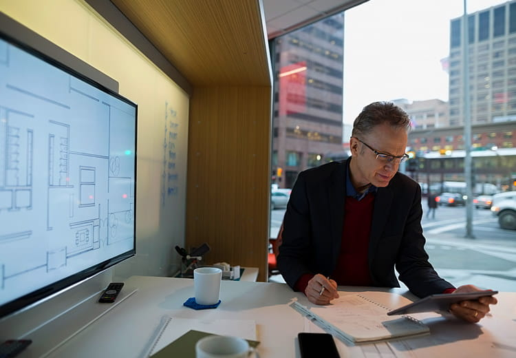 Executive reviews material on his tablet with large display on his right and an window on the city to his left