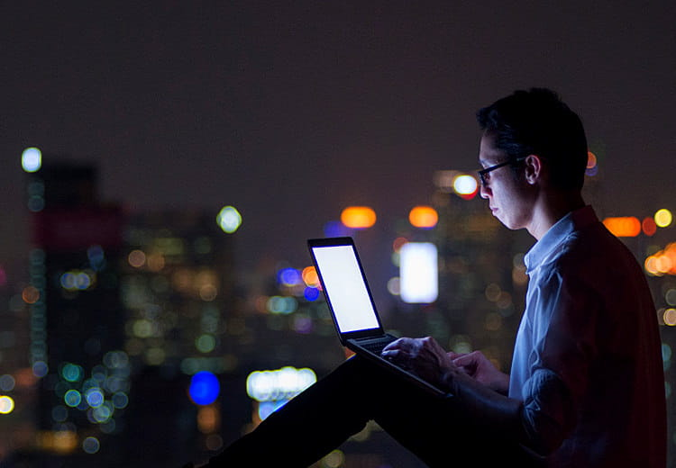 Man working on laptop at night with SAP Ariba e-procurement solutions