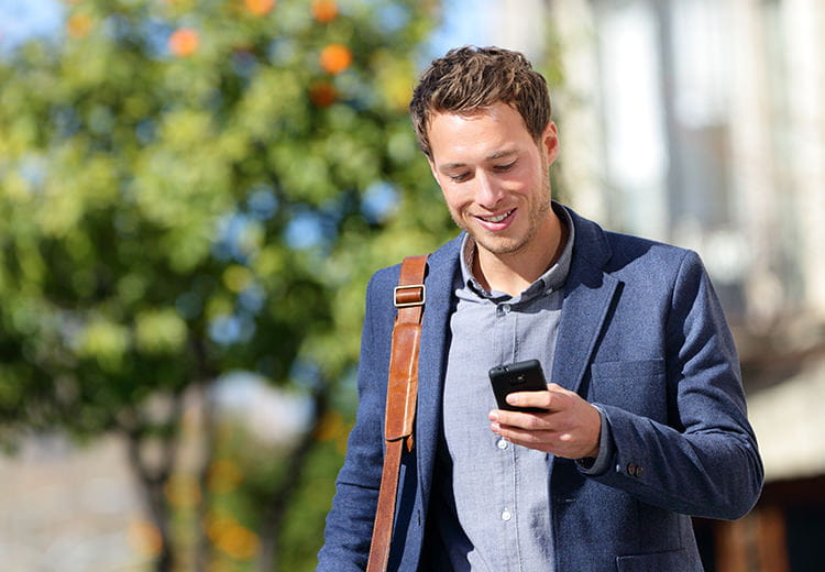 Man in blue blazer looking at phone
